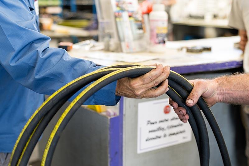 Remise de flexibles à un client dans notre magasin atelier